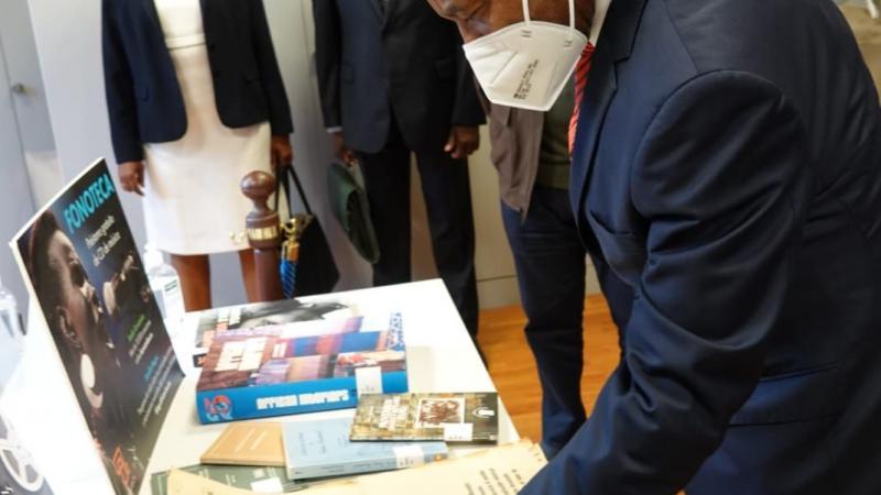 """El embajador de Guinea Ecuatorial en España visita Casa África. Aquí la delegación en la mediateca de Casa África, que cuenta con numerosas publicaciones del país.El embajador ojea antiguos ejemplares de """"Ébano"""", periódico de Guinea Ecuatorial que inició su edición en 1939, durante el periodo colonial español."""